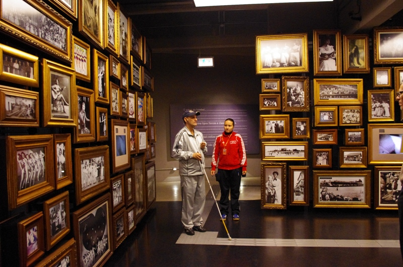 Um homem anda sobre o piso podotátil de uma das salas do Museu do Futebol usando um bastão para orientar o percurso.