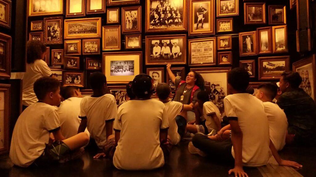 Crianças sentadas numa sala cercada por várias fotos antigas com molduras de madeira. Uma educadora com colete vermelho aponta uma das fotos e explica algo para o grupo.