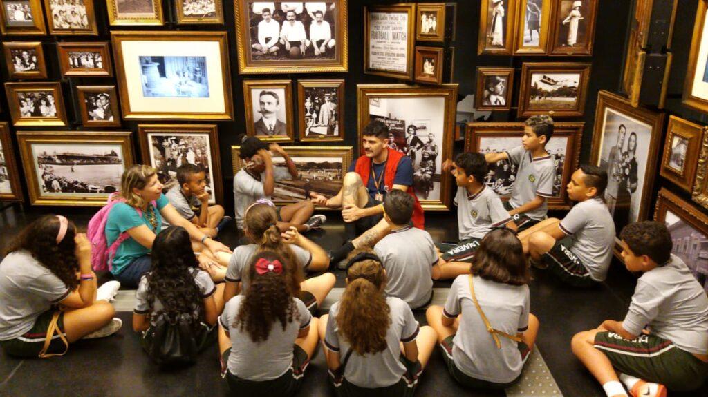 Grupo de crianças sentada no chão de uma sala cheia de fotos em preto e branco. Elas escutam um rapaz de colete vermelho, educador do museu, que também está sentado no chão.