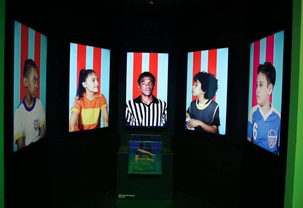 Cinco telas de TV na vertical, cada uma com a imagem de uma criança. No centro, um menino negro com uma camisa de time, com listras brancas e pretas. No centro, uma vitrine com uma caixa de sapato.