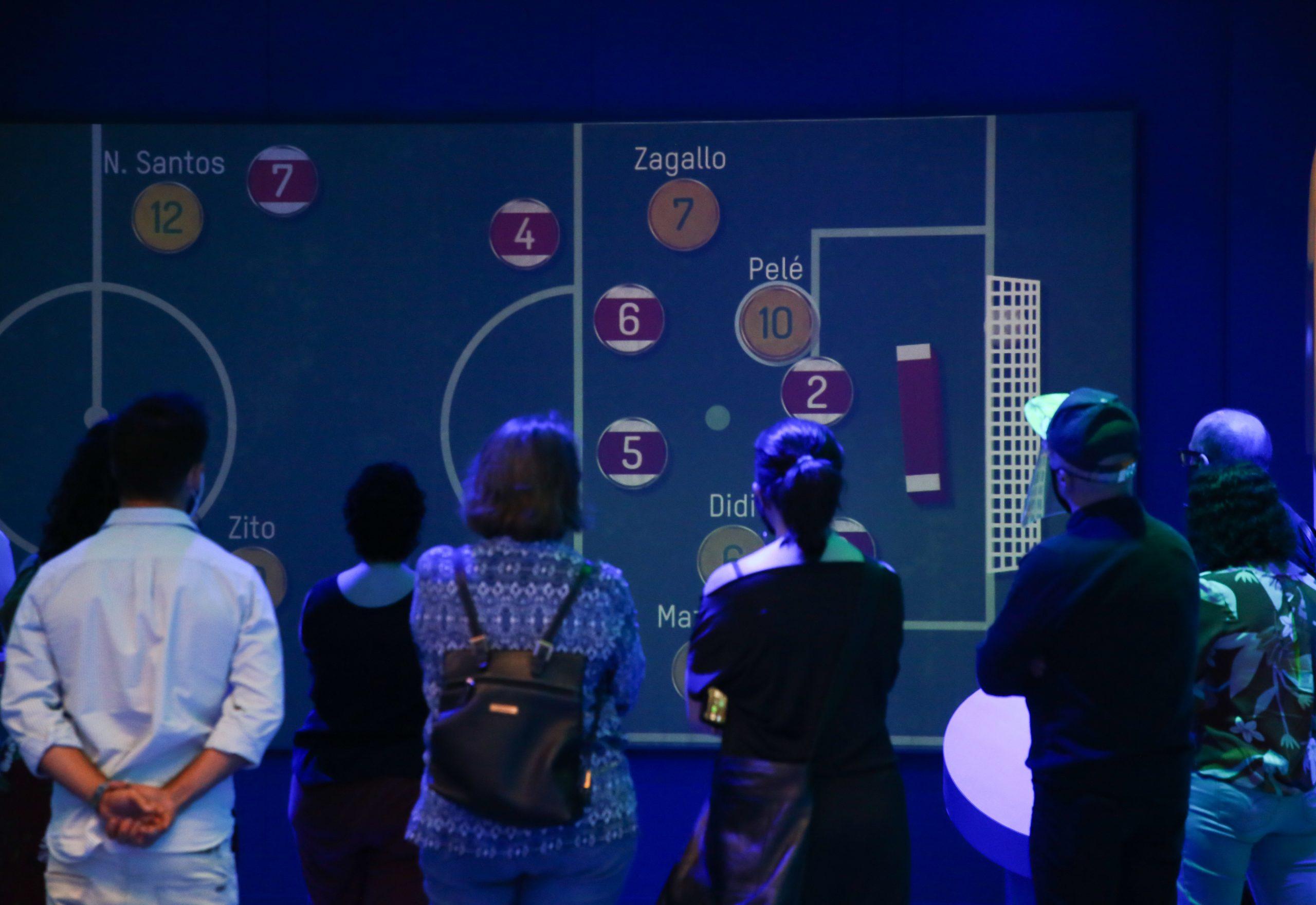 Pessoas de costas assistem numa tela um vídeo com um jogo de botão.