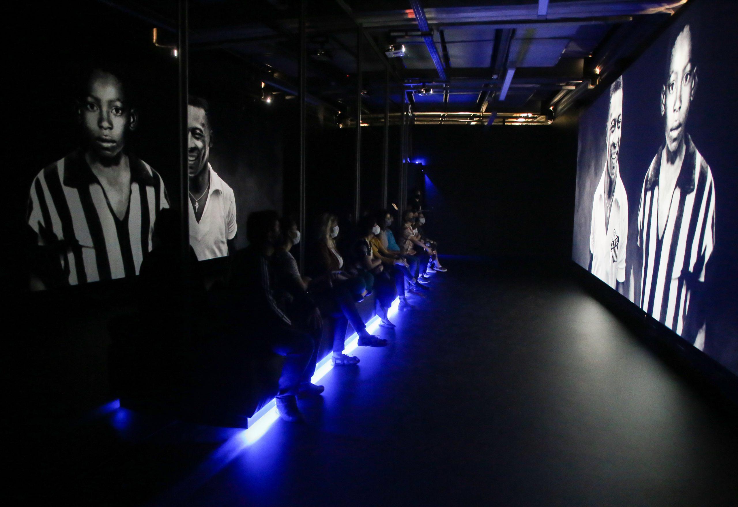 Numa sala escura, pessoas assistem um filme numa telão. O banco onde estão sentadas tem uma luz azul por baixo. Na tela, vemos uma foto de Pelé adolescente.
