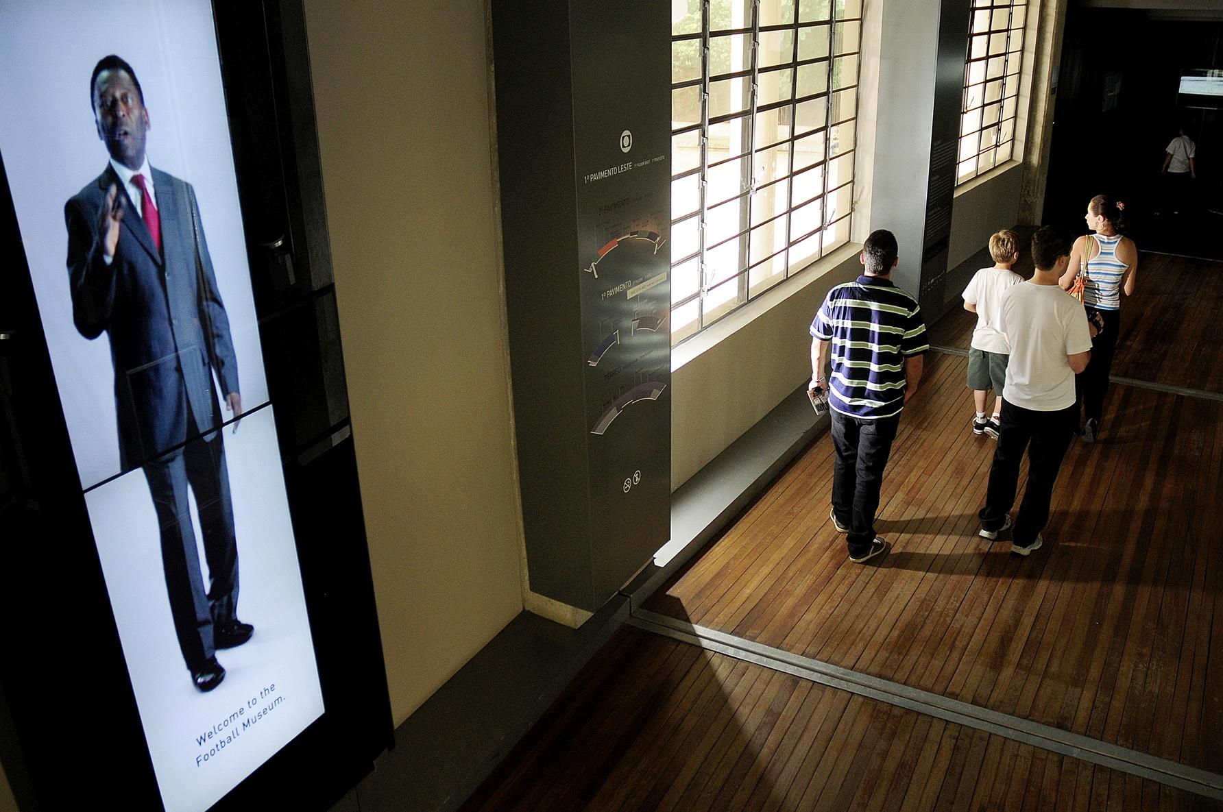 Parte de cima da entrada do Museu do Futebol. Recepção do Pelé em uma tela digital dando boas vindas aos visitantes. Depois dele, pessoas caminhando em direção ao Museu.