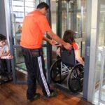 Funcionário do Educativo do Museu auxiliando uma mulher com cadeira de rodas a entrar no elevador enquanto outro rapaz também de cadeira de rodas, segura a porta do elevador