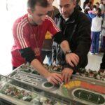 Três pessoas na foto. Um educador auxiliando um outro rapaz a tocar na maquete do estádio do Pacaembu com crianças no fundo.