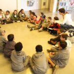 CriCrianças sentadas em círculo ouvindo atentamente uma mulher falando.