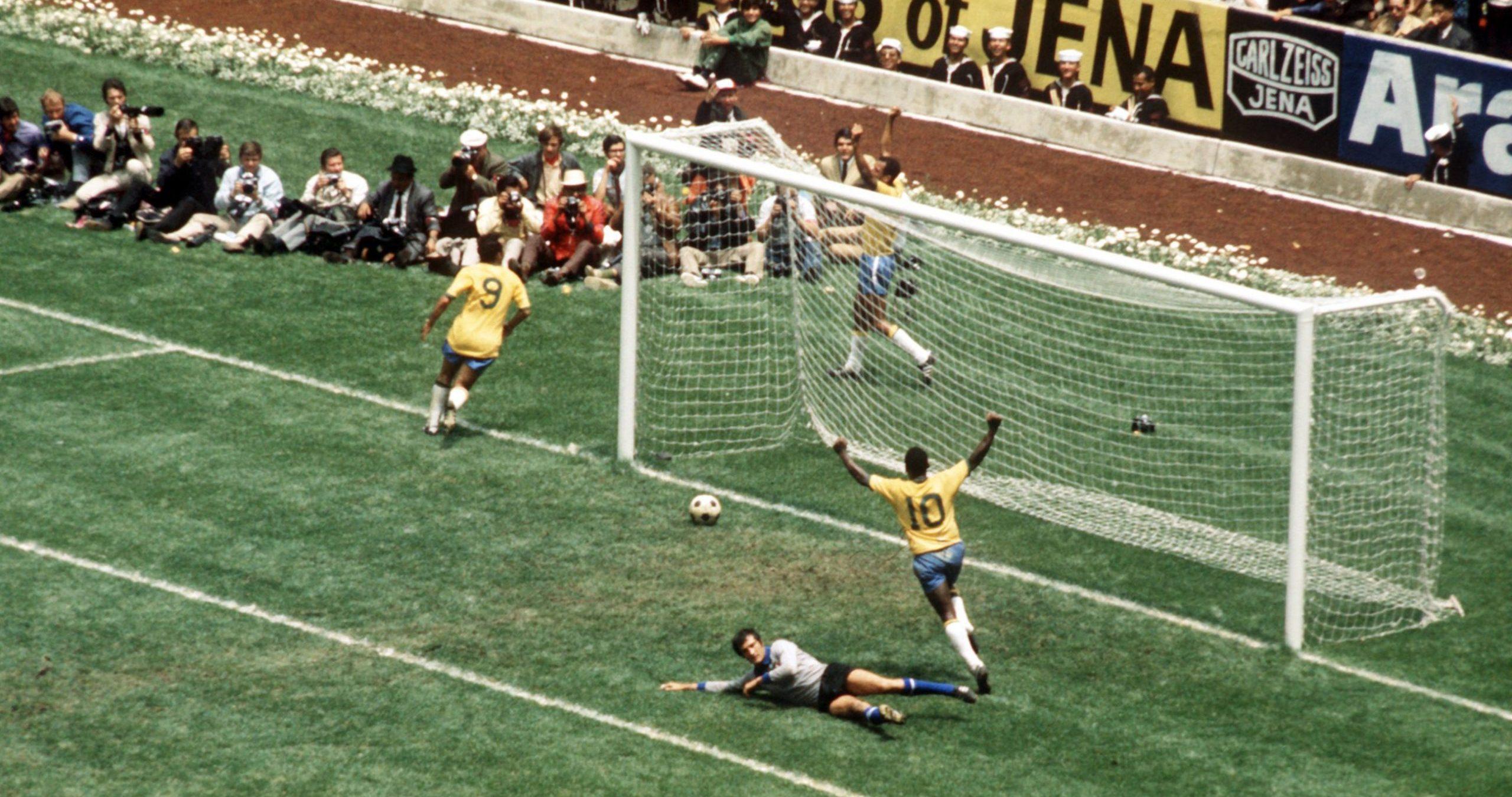 Pelé de costas levanta os braços em comemoração a um gol, com a bola ainda por passar a linha. O goleiro adversário está no chão.