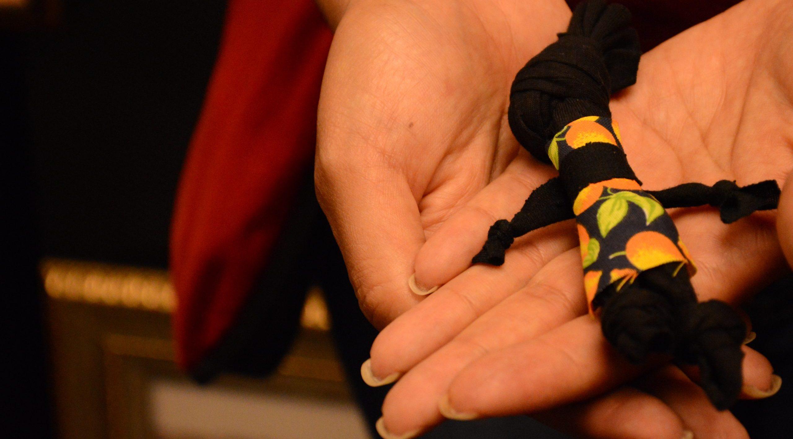 Close nas mãos de uma mulher que segura uma Abayomi, boneca negra feita de pano.