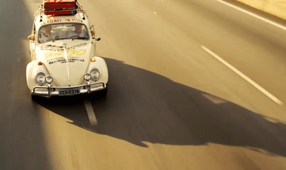 Um fusca branco fotografado na estrada, com sua sombra projetada no asfalto, num fim de tarde.