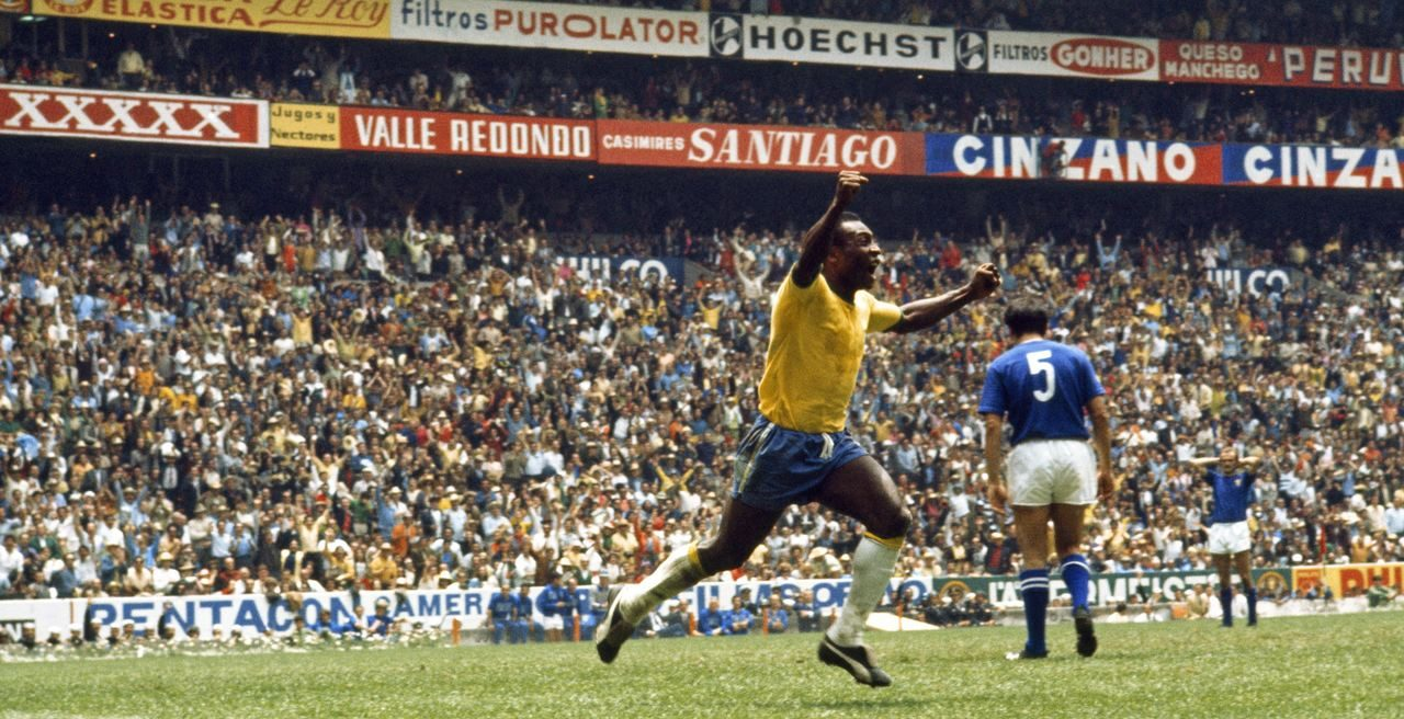 Pelé, vestido com a camisa da Seleção Brasileira, comemora um gol. Atrás dele há um estádio lotado.