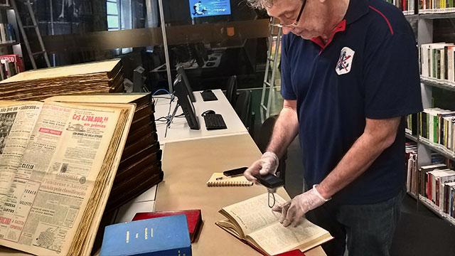 Um homem de pé fotografa a página de um livro. Ele usa luvas.