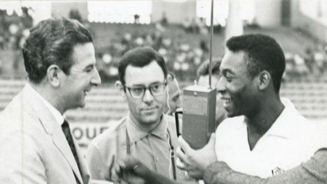 Foto em preto e branco de Pelé, sendo entrevistado por jornalistas em campo.