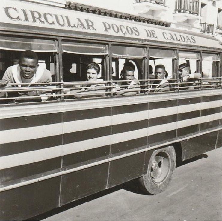 """Jogadores da Seleção Brasileira olham pela janela de um ônibus pintado com """"Circular Poços de Caldas"""" na lataria."""