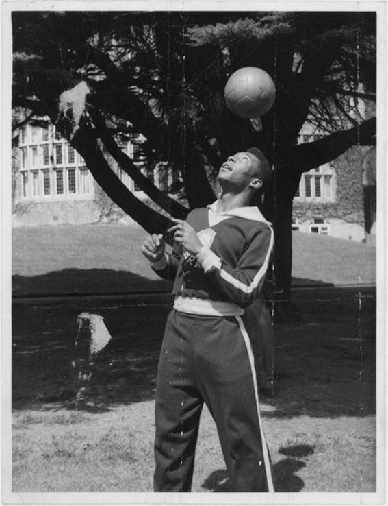 Com agasalho da Seleção Brasileira, Pelé domina uma bola com a cabeça.