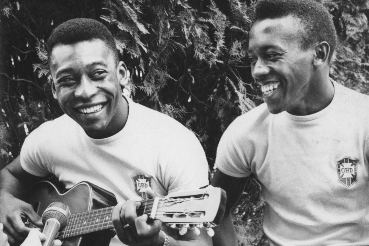 Pele toca violão ao lado de Ivair. Eles estão bastante sorridenters e vestem camisas da CBD.