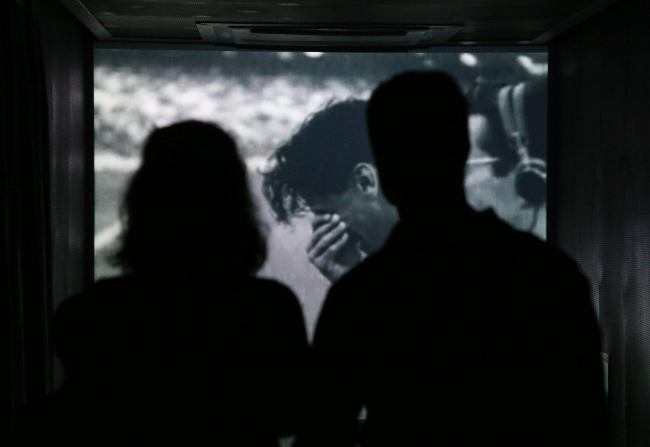 Sala Rito de Passagem: um homem e uma mulher de costas, em contraluz, observam de pé a imagem projetada na parede à frente deles de um homem chorando com a mão no rosto.