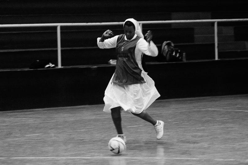 Uma mulher negra com vestes de freira domina uma bola com os pés em uma quadra. Sobre o hábito ela veste o colete do time.