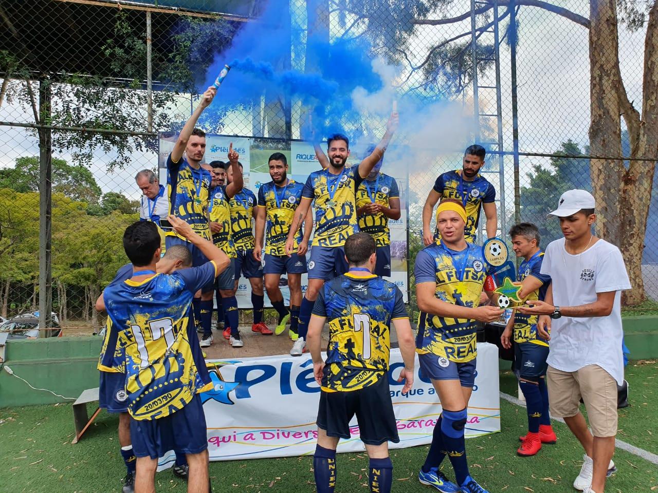 Um grupo de rapazes com uniforme azul e amarelo comemora um título em um pódio. Eles estão alegres e alguns têm nas mãos sinalizadores que soltam fumaça azul.