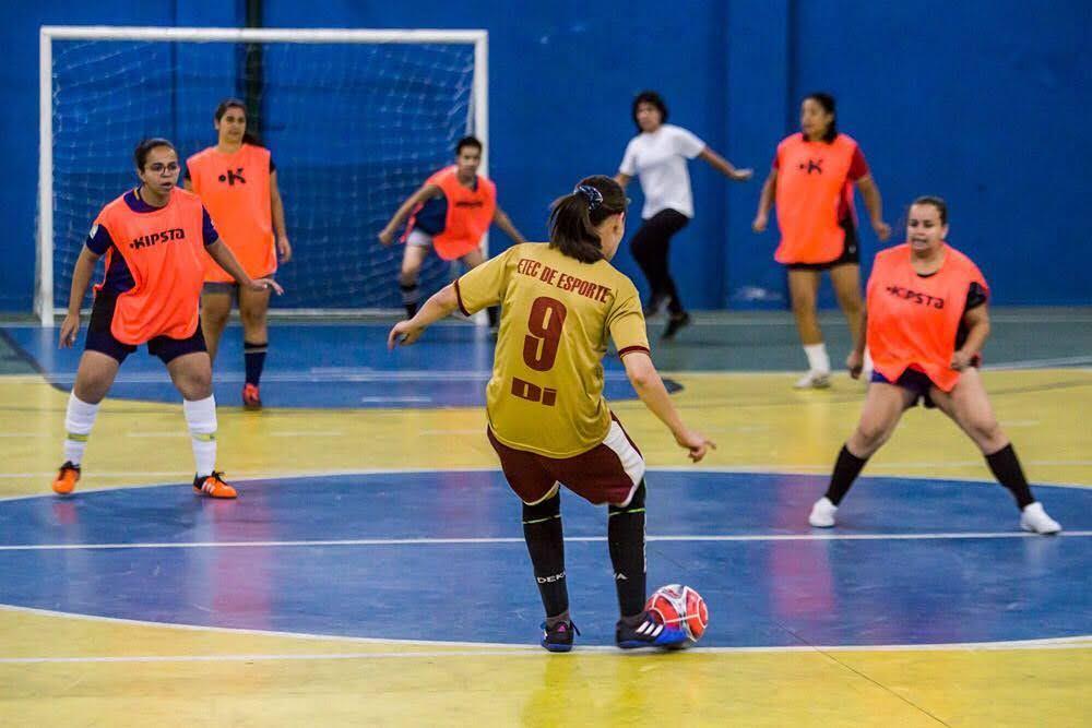 Um grupo de mulheres joga bola em uma quadra. Vemos uma atacante de costas com camisa amarela e a bola no pé. O outro time veste laranja e se prepara para defender a jogada.