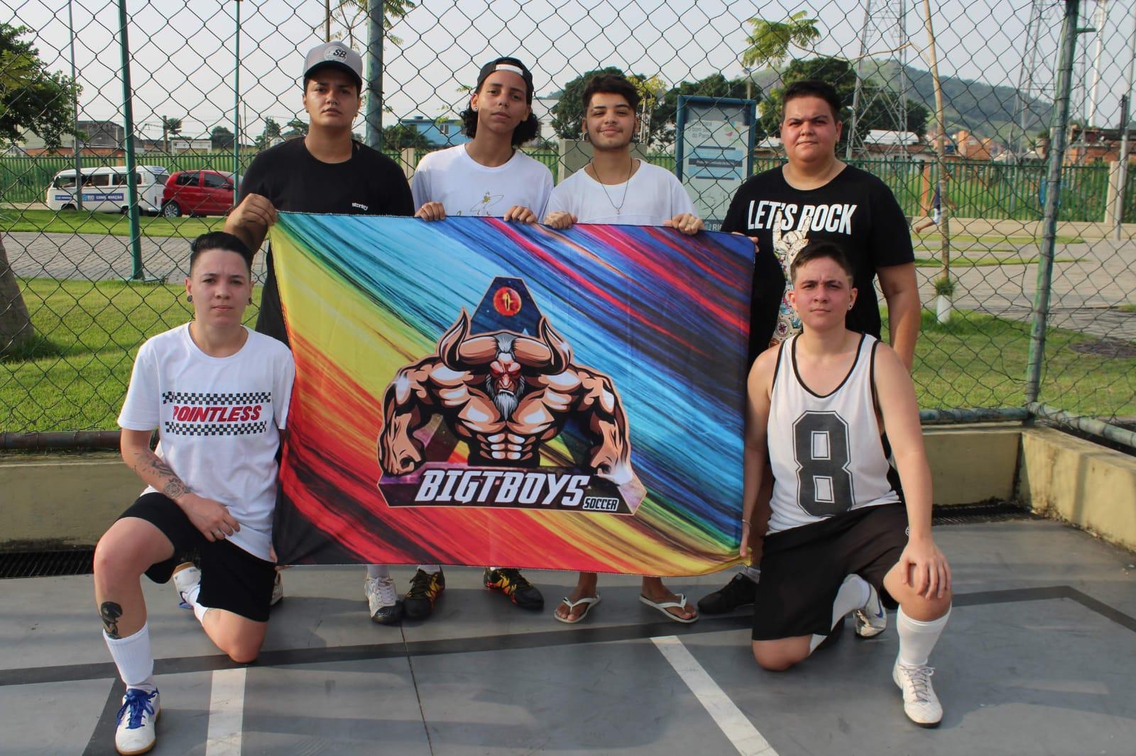 Um grupo de rapazes posa para foto segurando uma bandeira do time, os BigTBoys. A bandeira mostra um personagem musculoso e, por trás dele, as cores do arco-íris.