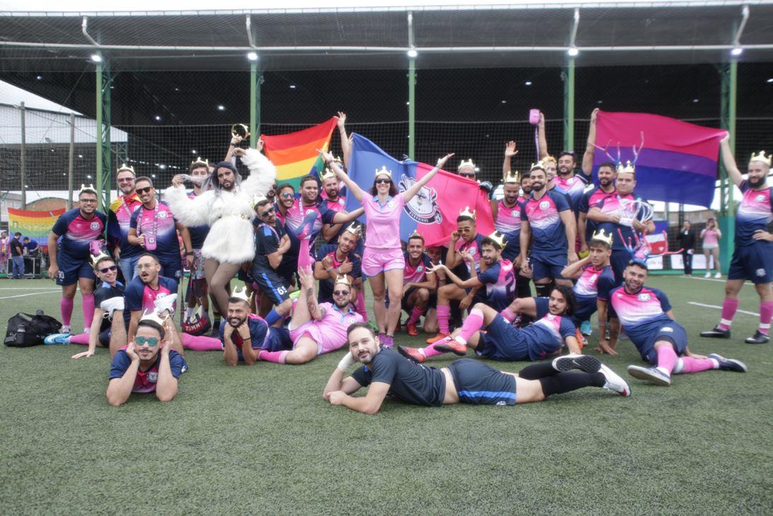 Um time de futebol composto por homens e mulheres posa para foto em um gramado. Muitos dos rapazes estão deitados na grama e fazem poses engraçadas. Atrás deles, aparecem bandeiras do arco-íris, símbolo do orgulho LGBT.
