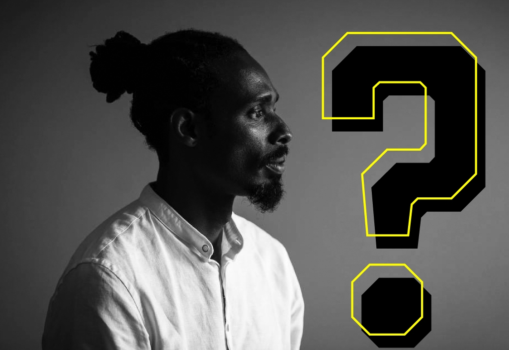 Diogo Silva, um homem negro com cabelo preso atrás da cabeça e cavanhaque, fotografado de lado, em preto e branco. Sobre a foto há o desenho de uma grande interrogação preta e amarela.