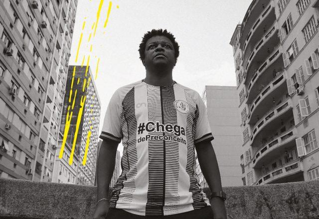 """Marcelo Carvalho, um homem negro, numa foto em preto e branco em ambiente urbano, veste uma camisa onde está escrito """"Chega de discriminação"""""""